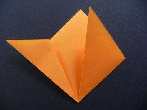 5. Take one of those points and fold it so the edge aligns with the side of the square.