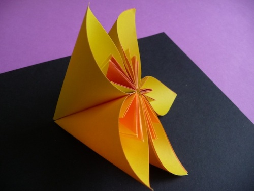 13. Apply glue or double sided tape along one of the outside edges. Press against the edge of another petal, making sure the top and bottom are properly aligned. Continue until all five petals are attached. If you decide to make a kusudama flower, you will need to make 12 more of these smaller flowers.